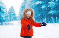 Cheerful child having fun outdoors with snowball in winter