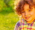 Cheerful child on summer field closeup portrait of adorable sweet nice little boy with curly hair having fun backyard happiness Royalty Free Stock Photos