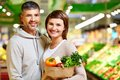 Cheerful consumers image of happy couple with healthy products looking at camera in supermarket Stock Photos