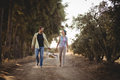 Cheerful couple carrying basket while walking on dirt road at olive farm Royalty Free Stock Photo