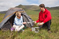 Cheerful couple cooking outdoors on camping trip in the countryside Stock Photography