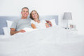 Cheerful couple cuddling in bed looking at camera Royalty Free Stock Photo