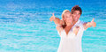 Cheerful couple enjoying beach vacation happy on the young family in love spending honeymoon on luxury islands active young people Stock Photos
