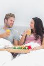 Cheerful couple having breakfast in bed with orange juice and cereals Royalty Free Stock Images