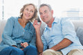 Cheerful couple listening to mobile phone together Royalty Free Stock Photo