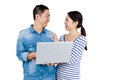 Cheerful couple looking at each other while holding laptop against white background Stock Photography