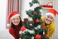 Cheerful couple looking out from Christmas tree Stock Photo