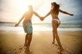 Cheerful couple in love run on the beach