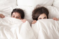 Cheerful couple lying in bed under covering looking at camera Royalty Free Stock Photo