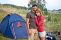 Cheerful couple photo of resting looking at camera in the countryside with tent on background Stock Photos