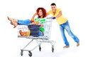 Cheerful couple shopping trolley isolated over white background Royalty Free Stock Photos