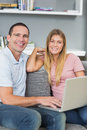 Cheerful couple sitting using laptop on the couch together in room at home Stock Photos