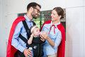 Cheerful couple in superhero costume feeding milk to daughter Royalty Free Stock Photo