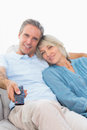 Cheerful couple on their couch watching tv at home in living room Royalty Free Stock Photo