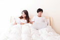 Cheerful couple using touch pad in bed and computer at home asian people Royalty Free Stock Images