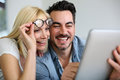 Cheerful couple websurfing on internet with tablet Royalty Free Stock Photos