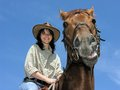 Cheerful cowgirl with dissatisfied horse Stock Images
