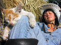 Cheerful cowgirl playing with funny kitten in the ranch in serie Royalty Free Stock Image