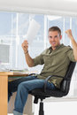 Cheerful creative business employee raising arms in a modern office Royalty Free Stock Image