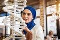 Cheerful curious muslim woman studying genomics