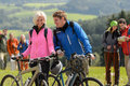 Cheerful cyclist couple with mountain bikes relaxing countryside Stock Image