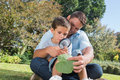 Cheerful dad and son inspecting leaf with a magnifying glass