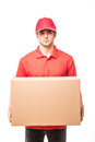 Cheerful delivery man happy young courier holding a cardboard box and smiling while standing on white background Royalty Free Stock Photo
