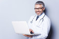 Cheerful doctor with laptop confident mature working on while standing against grey background Stock Images