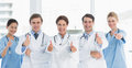 Cheerful doctors gesturing thumbs up at hospital Royalty Free Stock Photo