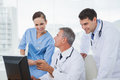 Cheerful doctors and surgeon working together on computer Royalty Free Stock Photo