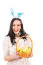 Cheerful easter woman with soap bubbles bunny ears holding basket and of are blowing out Stock Photo