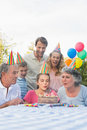 Cheerful extended family blowing out birthday candles together outside at picnic table Stock Images