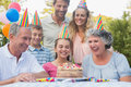 Cheerful extended family celebrating a birthday outside at picnic table Stock Image