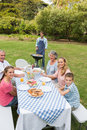 Cheerful extended family having a barbecue outside smiling at camer Royalty Free Stock Photo