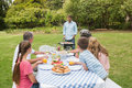Cheerful extended family watching father at the barbecue sitting picnic table Stock Photography