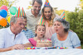 Cheerful extended family watching girl blowing out birthday cand candles outside at picnic table Royalty Free Stock Images