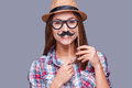 Cheerful fake face young woman in funky hat holding mustache and glasses on her and looking at camera while standing against Stock Photography