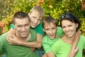 Cheerful family in green shirts walking the summer park Royalty Free Stock Photos