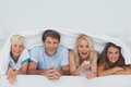 Cheerful family hiding under the blanket young Royalty Free Stock Photo