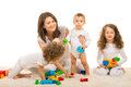 Cheerful family home of mother and three kids sitting on carpet with toys Stock Images