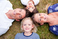 Cheerful family lying in circle on the grass Stock Images