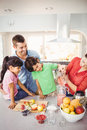 Cheerful family with mother pouring fruit juice in jug Royalty Free Stock Photo
