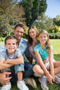 Cheerful family relaxing outside in the park smiling at camera Stock Images