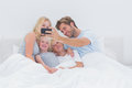 Cheerful family taking self pictures with a smartphone in bed Royalty Free Stock Images