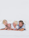 Cheerful family under the duvet at home in bed Stock Images