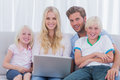 Cheerful family using a laptop sat on the couch Royalty Free Stock Photography