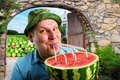 Cheerful farmer drinking watermelon juice through a tubules Stock Image