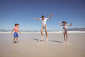 Cheerful father with children jumping on shore at beach Royalty Free Stock Photo