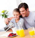 Cheerful father and his daughter having breakfast Royalty Free Stock Photos