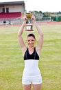 Cheerful female athlete holding a trophee Royalty Free Stock Images